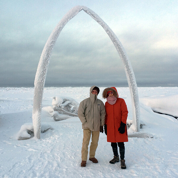 People standing in front of a bowhead whale jaw bone on a frozen beach.